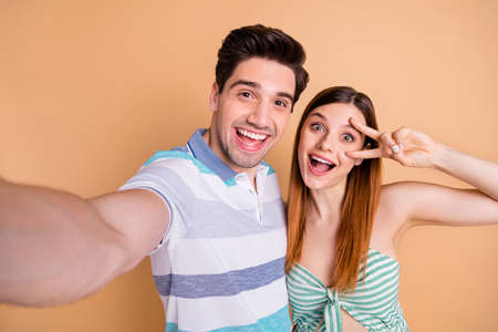 Closeup photo of pretty wife lady and handsome husband guy married couple spend time together take selfies good mood show v-sign symbol wear casual clothes isolated pastel beige color background Stock Photo