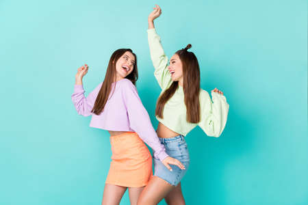 Photo of two cheerful lady girlfriends celebrate student party cool clothes dance favorite song wear cropped sweaters naked belly short skirts isolated pastel teal color background