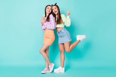 Full body photo of two cheerful ladies best friends cool look clothes hug show v-sign symbol wear cropped sweaters naked belly short skirts shoes isolated pastel teal color background
