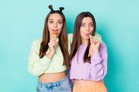 Photo of two crazy funny cheerful ladies hold lollipop chupa chups hands childish mood tasty sweets wear cropped pullovers naked belly skirts isolated pastel teal color background