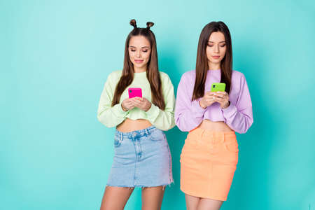 Photo of two cool funny sisters ladies best friends looking telephone hands chatting each other wear cropped sweaters naked belly short skirts isolated pastel teal color background Reklamní fotografie