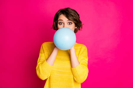 Portrait of cute funny lovely youth girl have festive occasion prepare, party blow inflate balloon wear vivid jumper isolated over shine color background