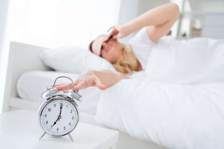 Profile photo of displeased lady lying sleeping bed white sheets blanket metal alarm clock ringing sever oclock morning turning off sound work monday wear pajama room indoors