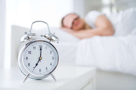 Profile photo of charming lady lying sleeping bed white sheets blanket, clothes calm sure metal alarm clock will ring at sever o'clock morning work monday wear pajama room indoors Reklamní fotografie