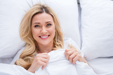 High angle above view closeup photo of charming blond lady lying linen bed covered blanket enjoy weekend saturday morning quarantine time stay home wear pajama room indoors