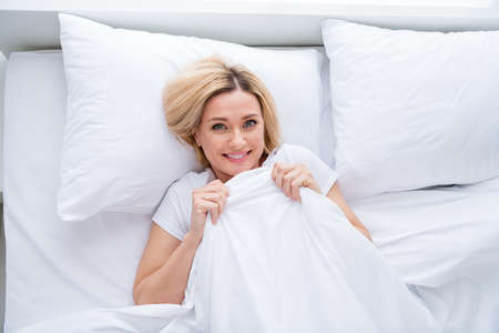 High angle above view photo of charming blond lady lying linen bed covered blanket enjoy weekend saturday morning quarantine time stay home wear pajama room indoors