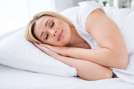 Profile photo of charming blond house wife lady lying sheets bed covered blanket hold hands under head eyes closed weekend saturday morning quarantine wear pajama room indoors