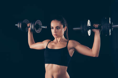 Close up photo of charming sportive woman hold hand have muscles true power lifter isolated over black background Stock Photo