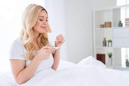 Photo of cheerful beautiful lady lying cozy linen quarantine time white sheets blanket amazing energetic morning good mood smell fresh hot coffee overjoyed stay home wear pajama indoors