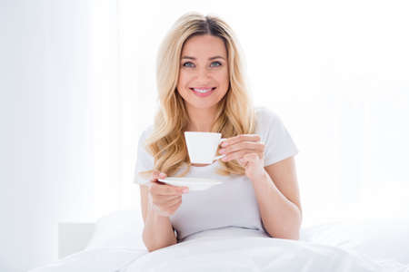 Photo of cheerful beautiful lady lying cozy bed linen quarantine time white sheets blanket amazing energetic morning good mood drink fresh hot coffee stay home wear pajama room indoors