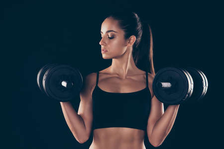 Close up photo of lovely woman hold hand barbells look feel focused hair brunette hairstyle ponytail isolated over black background Reklamní fotografie