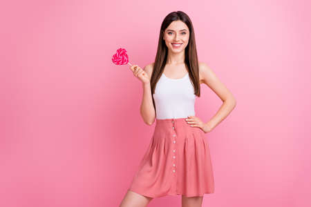 Photo of charming funny lady hold big heart shape lollipop on stick good mood nice day wear white singlet dotted short skirt isolated pastel pink color background
