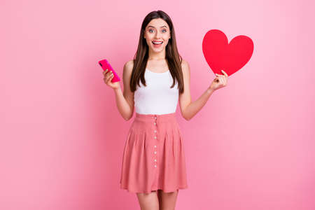 Photo of attractive amazed lady hold telephone red paper heart check likes instagram wear casual white singlet short summer dotted skirt isolated pastel pink color background Reklamní fotografie
