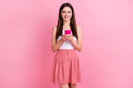 Portrait of nice-looking attractive lovely charming pretty cheerful cheery straight-haired girl using digital device web service app 5g isolated over pink pastel color background Reklamní fotografie