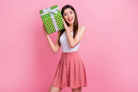 Photo of charming funny lady hold big green dotted bow gift box hands try to guess what inside wear white singlet short dotted skirt isolated pastel pink color background Foto de archivo