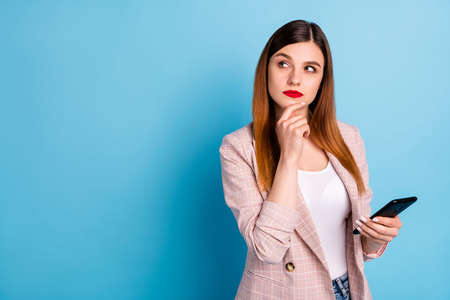 Portrait of minded pensive girl ceo marketer want post comment use smartphone look copyspace think thoughts touch chin hand wear checkered blazer isolated over blue color background