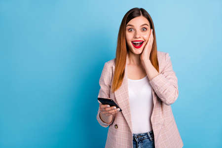 Astonished positive girl blogger use smartphone impressed social media like comment repost share notification touch hand face wear checkered blazer isolated blue color background