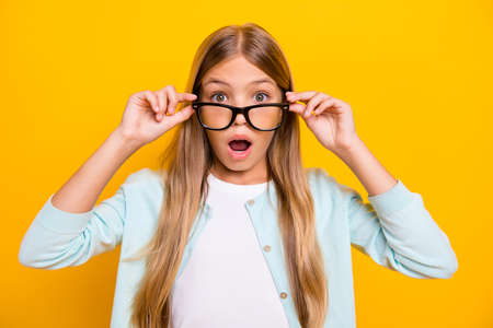 Photo of beautiful pretty little blond lady diligent student pupil take off glasses open mouth see bad grade mark year wear specs casual shirt isolated yellow bright color background 免版税图像
