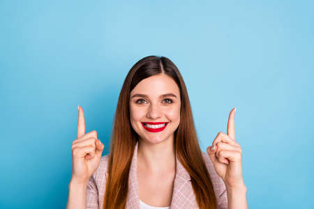 Portrait of positive confident girl promoter point index finger up copyspace present ads promotion suggest select option wear good look clothes isolated over blue color background