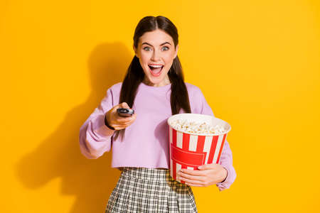 Portrait cheerful energetic girl ready watch favorite series switch remote, control hold big pop corn box wear style stylish trendy plaid pullover isolated bright shine color background Stock Photo