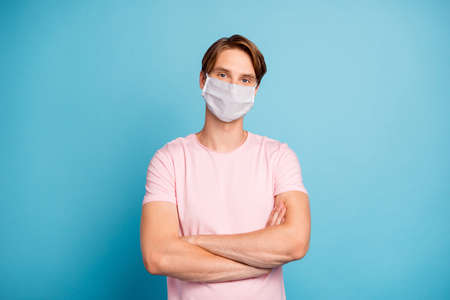 Portrait of his he nice virile masculine youth guy folded arms wearing safety mask, stay home social distance self isolation flu flue grippe contamination healthcare isolated over blue color background