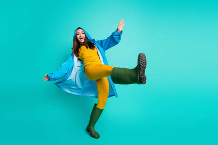 Full body photo of attractive funny lady cheerful mood rainy weather, street walk hood on head go through puddles wear raincoat sweater pants gum boots isolated teal color background 免版税图像