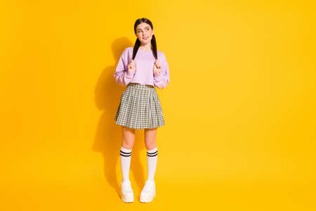 Full length body size view of her she nice attractive lovely pretty charming shy cheery girl posing thinking biting lip isolated on bright vivid shine vibrant yellow color background 写真素材