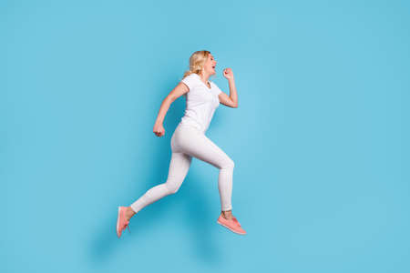 Full length profile photo of attractive funny crazy lady jump high up running speed rushing shopping center wear casual white s-shirt pants footwear isolated blue color background