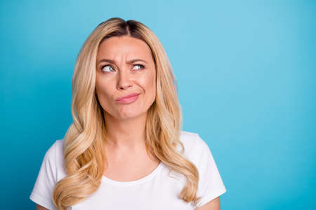 Closeup photo of attractive lady wavy blond hairdo doubtful facial expression look empty space hesitate difficult decision wear casual white s-shirt isolated blue color background