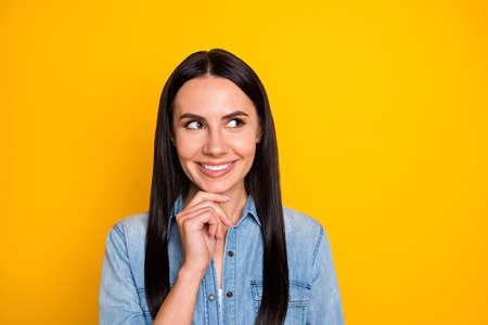 Close-up portrait of her she nice-looking attractive lovely pretty cute curious cheerful long-haired girl guessing clue touching chin isolated on bright vivid shine vibrant yellow color background 写真素材