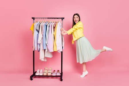 I want all this. Full length photo of pretty lady showroom fashion collection choosing clothes wear trend yellow leather jacket long skirt shoes isolated pastel pink color background Stok Fotoğraf