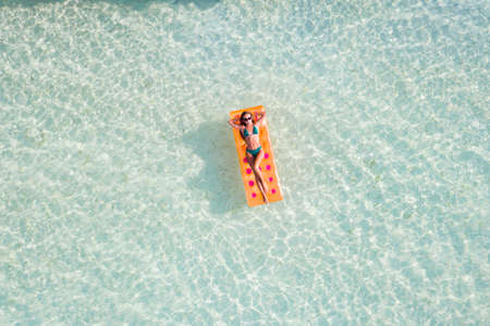 Top above high angle aerial drone view of fit slim thin slender attractive girl floating on rubber mattress clear sea water leisure sunny, weather taking sun bath spending celebrating birthday weekend