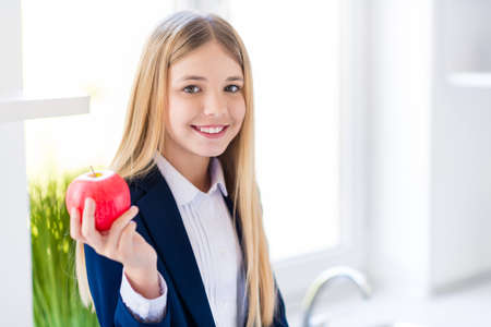 Close-up portrait of nice attractive pretty lovely cute cheerful small little long-haired girl eating fresh natural apple useful vitamin after classes in light white house kitchen indoors
