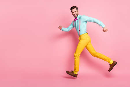 Full length photo of cheerful crazy guy enjoy rejoice discount jump run copyspace wear shirt pants isolated over pastel color background