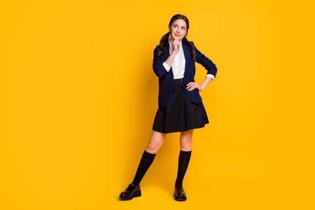 Full length photo of minded high school student girl touch hand chin look copyspace decide lesson courses decision wear black jacket blazer skirt isolated bright shine color background 写真素材