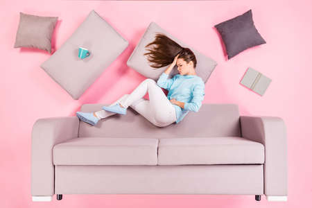 depressed girl lying on divan feeling bad hurt injury belly tummy indigestion isolated on pink pastel color background