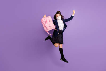 little long-haired girl jumping having fun wearing mask holiday isolated lilac violet purple pastel color background
