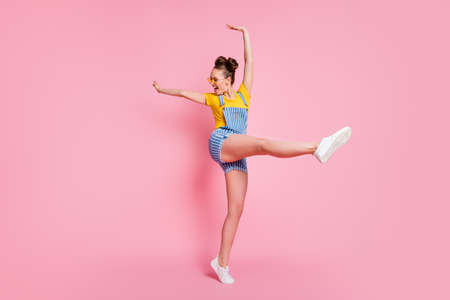 brown-haired girl jumping dancing having fun pirouette isolated on pink pastel color background 스톡 콘텐츠