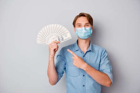 attractive guy wearing safety gauze mask holding in hands win winner deposit bet rate isolated over grey color background