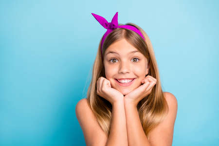 Portrait of content lovely cute pretty kid girl enjoy touch fist face wear colorful dress skirt isolated over blue color background Stock Photo