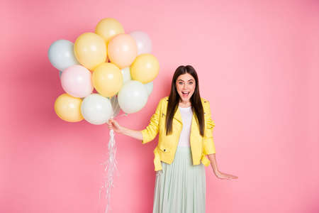 Portrait of her she nice-looking attractive pretty lovely cheerful cheery glad girl having fun holding in hands air balls isolated over bright vivid shine vibrant yellow color background
