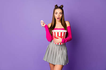 Photo of pretty terrified lady two buns eyes hold popcorn bucket watch horror movie wear pink off-shoulders cropped top plaid short skirt isolated pastel purple color background