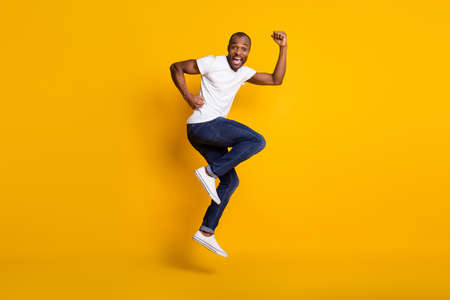 Full length body size view of his he nice attractive glad funny childish cheerful cherry guy jumping having fun dancing isolated over bright vivid shine vibrant yellow color background