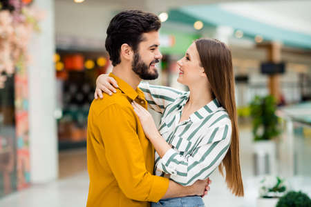 Profile side photo of positive gentle cute spouses girl husband hug cuddle enjoy valentine day rest relax wear yellow striped shirt in shopping mall center store