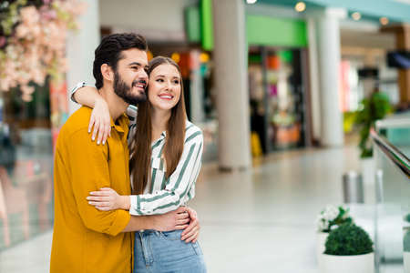 Portrait of positive tender gentle couple spouses man woman hug enjoy date in shopping mall center weekend rest wear striped yellow shirt