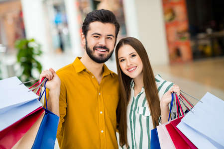 Portrait of positive cheerful comfort cozy two people married couple man woman have free time in shopping center hold many packages 50 sales wear yellow striped shirt