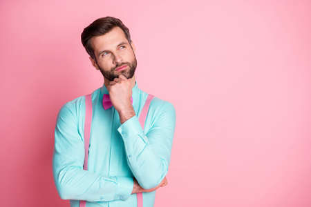 Photo of handsome guy trend clothes look side up empty space imagination flight arm on chin creative person wear shirt suspenders bow tie isolated pastel pink color background