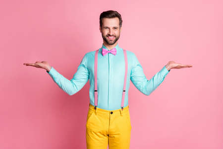 Portrait of positive cheerful guy promoter hold hand recommend suggest select advert option promo wear yellow pants trousers isolated over pastel color background