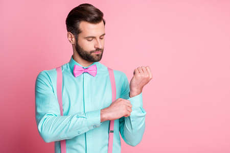 Close-up portrait of his he nice attractive imposing elegant well-dressed fashionable content bearded guy artist fixing button cufflink preparing isolated over pink pastel color background