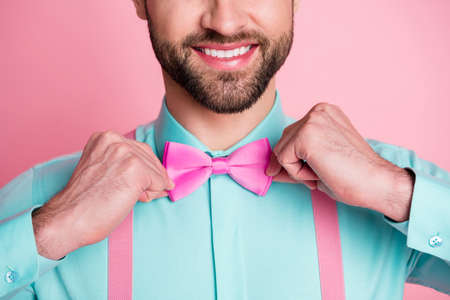 Close-up cropped view portrait of his he nice attractive content metrosexual elegant cheerful cheery imposing luxury brandy bearded guy artist fixing bow isolated over pink pastel color background